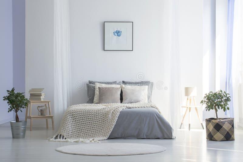 Round dywanik przed popielatym łóżkiem z koc w minimalnej sypialni ja fotografia stock