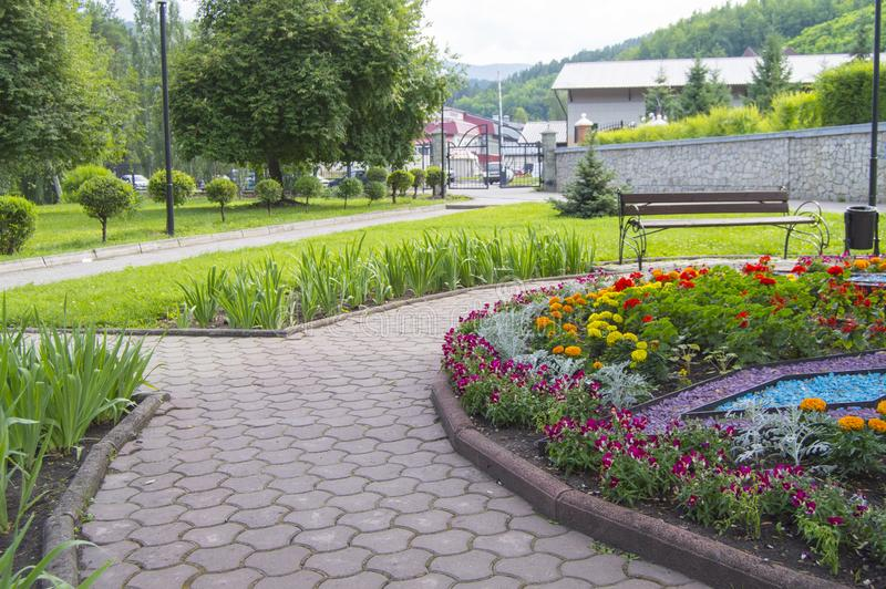 Round flower bed with colorful decorative flowers and plants, garden bench stands on the paving tiles, a beautiful recreation area. In the city Park, grass royalty free stock image