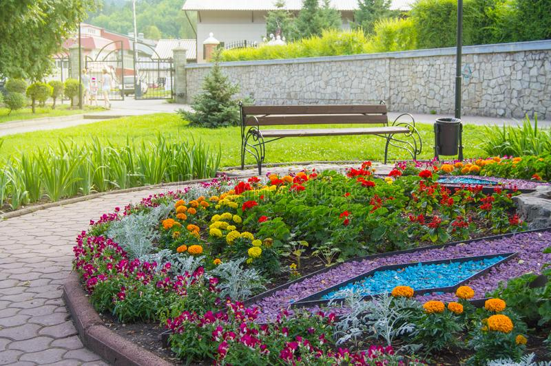 Round flower bed with colorful decorative flowers and plants, garden bench stands on the paving tiles, a beautiful recreation area. In the city Park, grass stock images