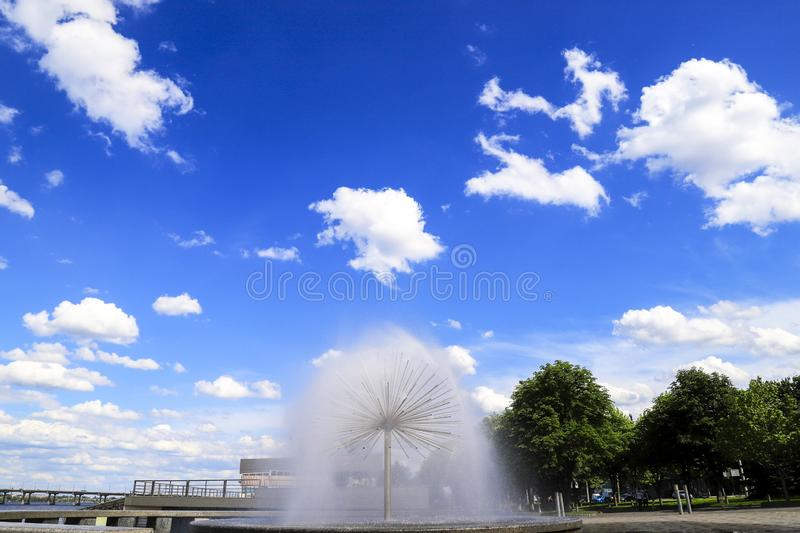 Round fountain in  Dnipro  city, beautiful clouds,  spring, summer cityscape. Dnepropetrovsk, Ukraine, space for text. Round fountain in  Dnipro  city against stock image