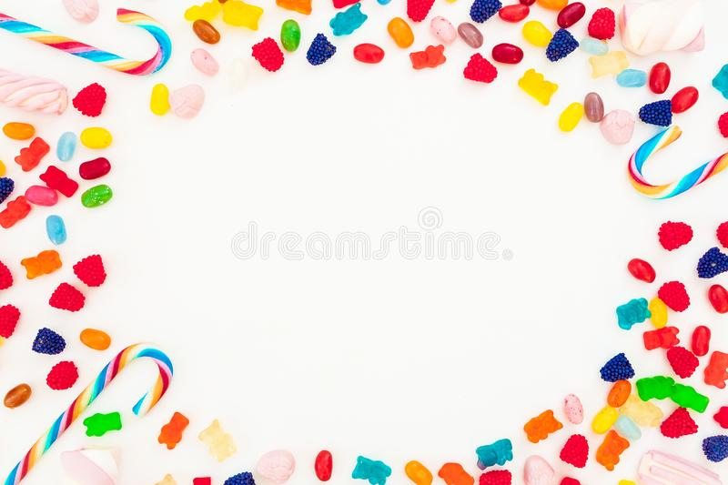 Round frame of assorted colored candy on white background. Flat lay, top view stock photography