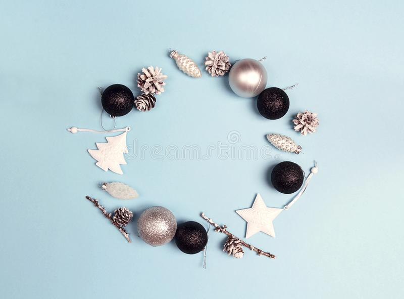 Round frame of Christmas decorations with copy space on blue background. Wreath composition of cones, balls, tree and star. royalty free stock image