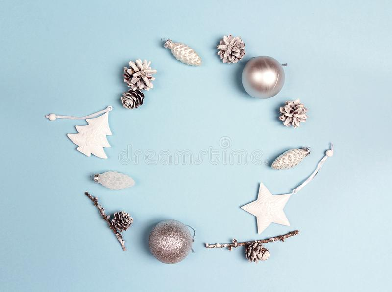 Round frame of Christmas decorations with copy space on blue background. Wreath composition of cones, balls,tree and star. royalty free stock image