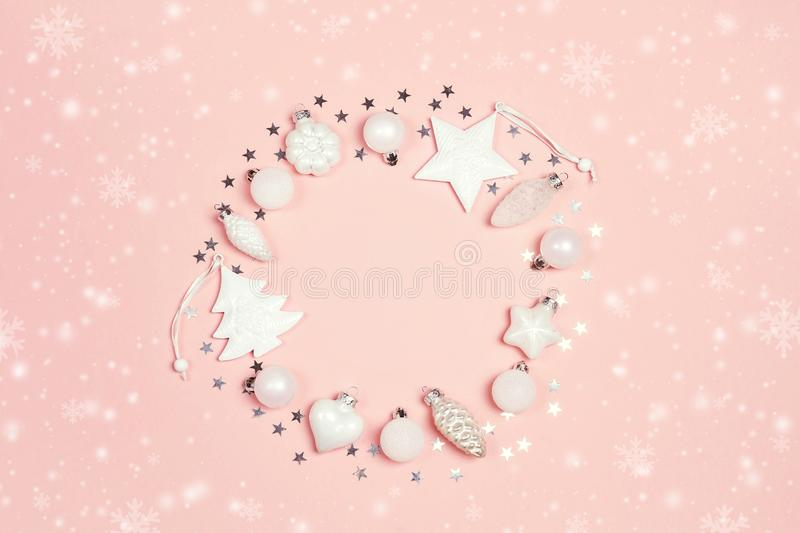 Round frame of Christmas decorations with copy space on pink background. Wreath composition of cones, balls,tree and star stock photo
