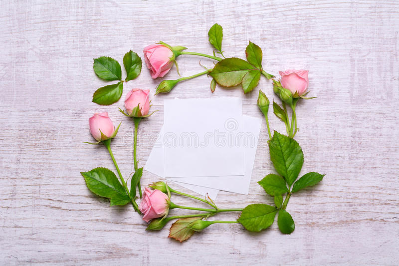 Round frame of delicate flowers. Pink roses on a wooden background. Paper with empty place for text royalty free stock photography
