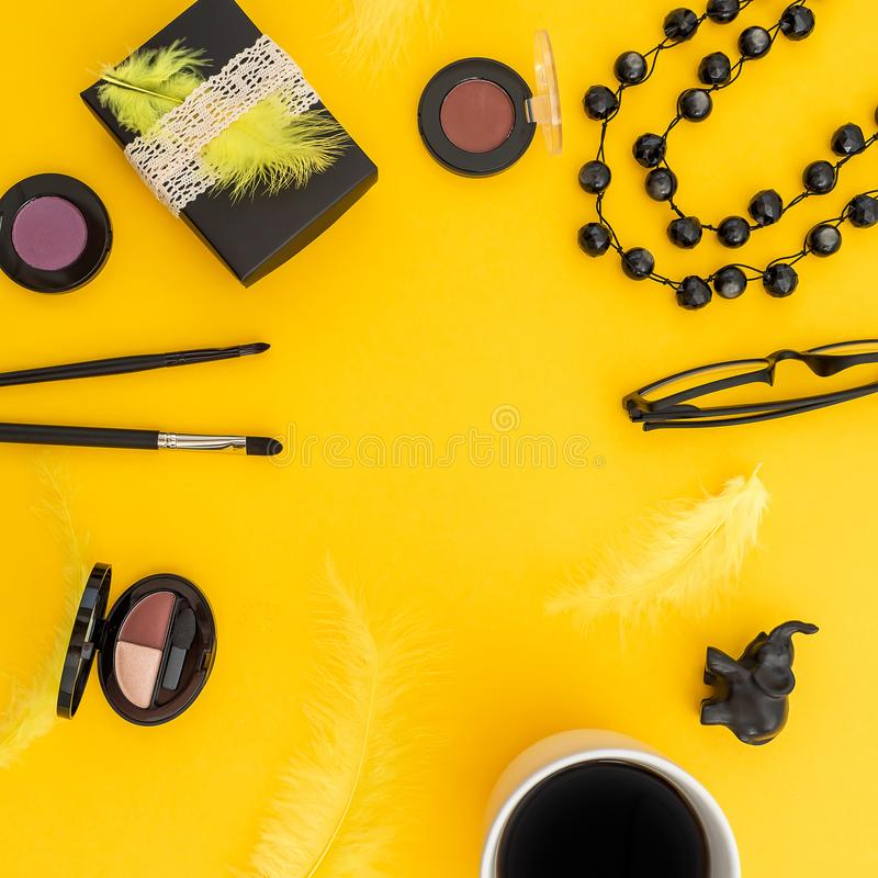 Round frame of gift box, glasses, cosmetics, bijouterie and accessories with mug of coffee on yellow background. Blogger concept w. Ith copy space stock photos