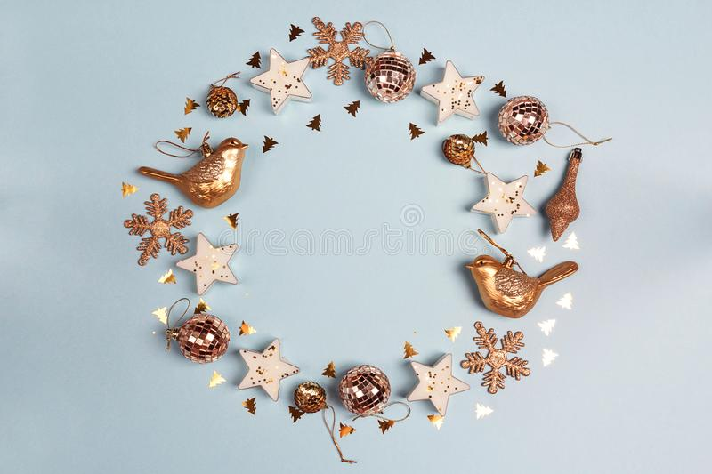 Round frame of golden Christmas decorations wit copy space on blue background. Top view, flat lay stock photos