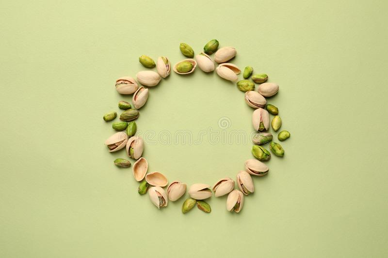 Round frame made of organic pistachio nuts on color background, top view. Space for text stock photo