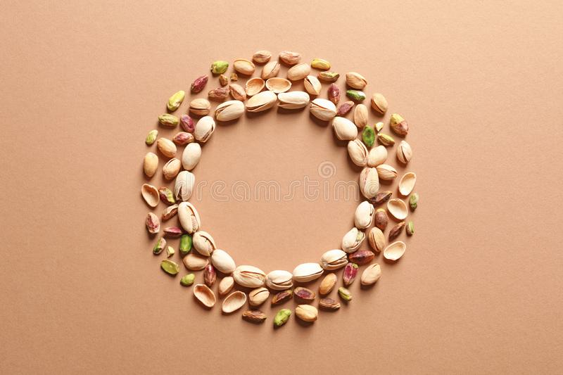 Round frame made of organic pistachio nuts, flat lay. Space for text royalty free stock photo