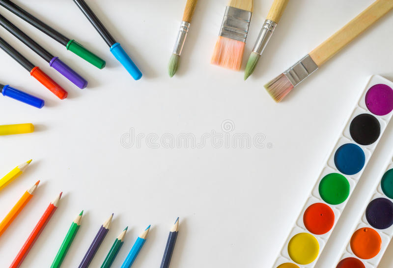 Round frame, made from painting brushes, felt-tip pens, watercolor paints, pencils on white background royalty free stock photo