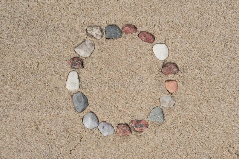 Round frame made of pebble stones on sand background stock image