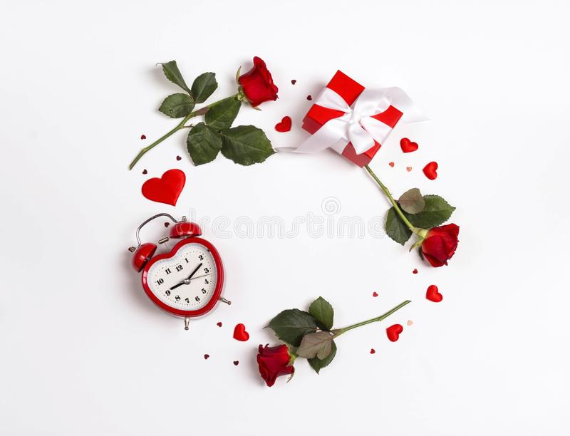 Round frame made of rose flowers, gifts, alarm clock and decorative hearts on white background. St. Valentines day background stock photography