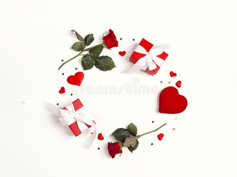 Round frame made of rose flowers, gifts and decorative hearts on white background. St. Valentines day background royalty free stock photography