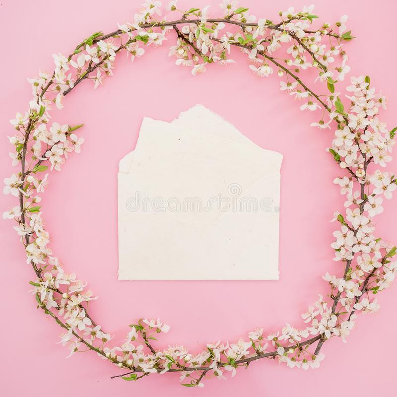 Round frame made of spring flowers and paper vintage envelope on pink background. Flat lay stock photo