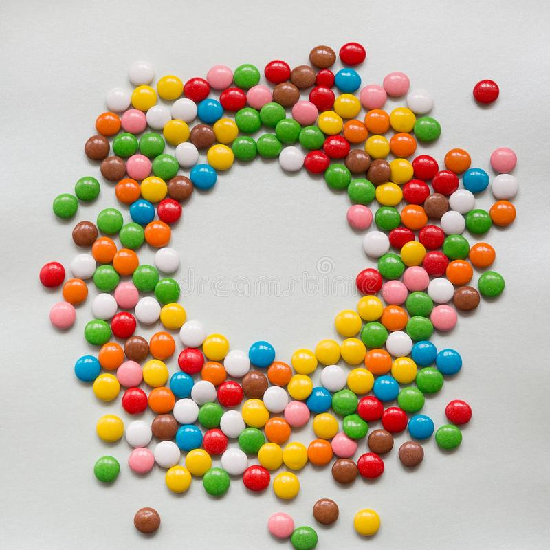 Round frame of many multicolored round candy in the glaze shell. Place to sign on a pale background. Holiday Web banner with copy space in shape of circle stock image