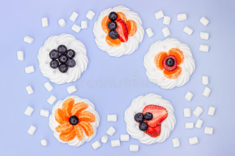 Round frame of meringue with blueberries, strawberries, marshmallow and tangerines on a lavender background. Top view stock image