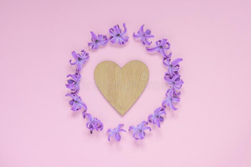 Round frame of pastel purple hyecinth flowers and wooden heart on gradient pink background. Floral wreath. Layout for holidays royalty free stock photography