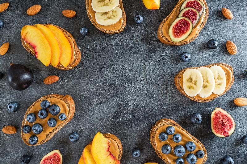 Round frame of sandwich with peanut butter, fresh fruits and berries. Healthy breakfast concept. Flat lay, top view royalty free stock image