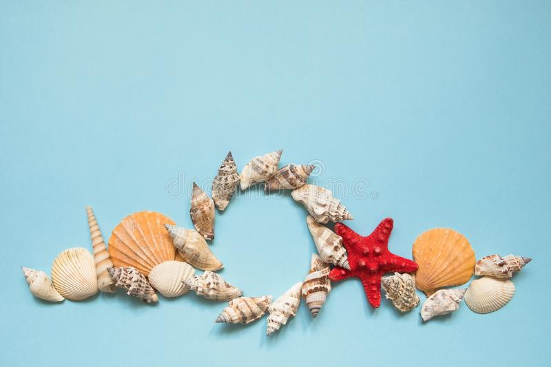 Round frame with seashells and red starfish on blue sea background with copy space. Beach vacation concept, cruise. royalty free stock photo