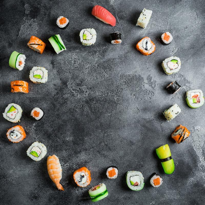 Round frame of set of Japanese food on dark background. Sushi rolls, nigiri, salmon steak, rice and avocado. Flat lay. Top view royalty free stock photography