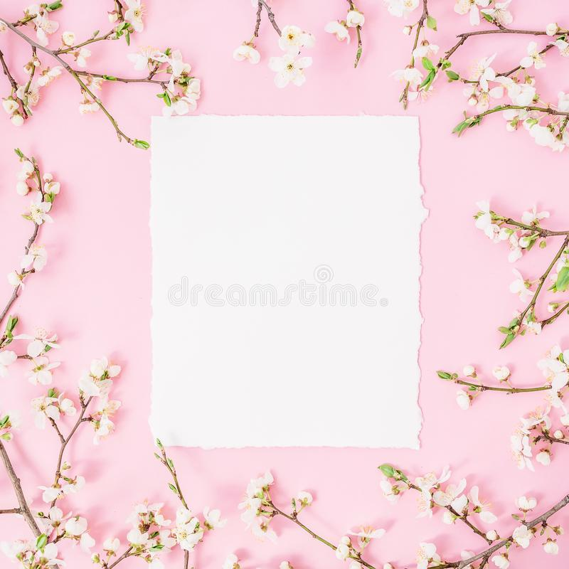 Round frame with spring flowers and white paper vintage car on pink background. Flat lay, top view. stock images