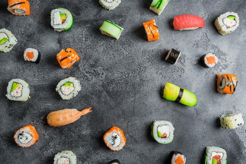Round frame of sushi rolls on a dark background. Japanese food frame. Flat lay. stock images