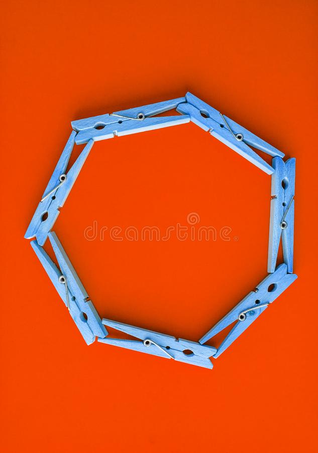 Round frame of wooden clothespins on color bright red and pink background. View from above. Copy space. Flat lay. The concept is. Natural, eco-friendly stock photography
