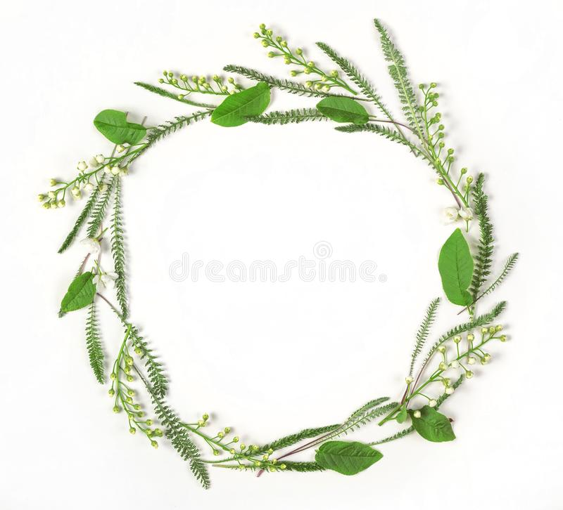 Round frame wreath made of spring flowers and leaves isolated on white background. Flat lay. royalty free stock photo