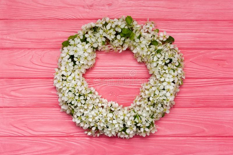 Round frame wreath made of spring flowers and leaves on pink wooden background. Flat lay. Top view. stock photos