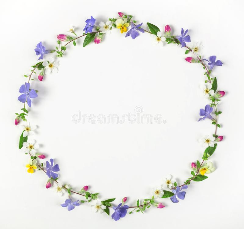 Round frame wreath made of spring wildflowers, lilac flowers, pink buds and leaves isolated on white background. royalty free stock photos