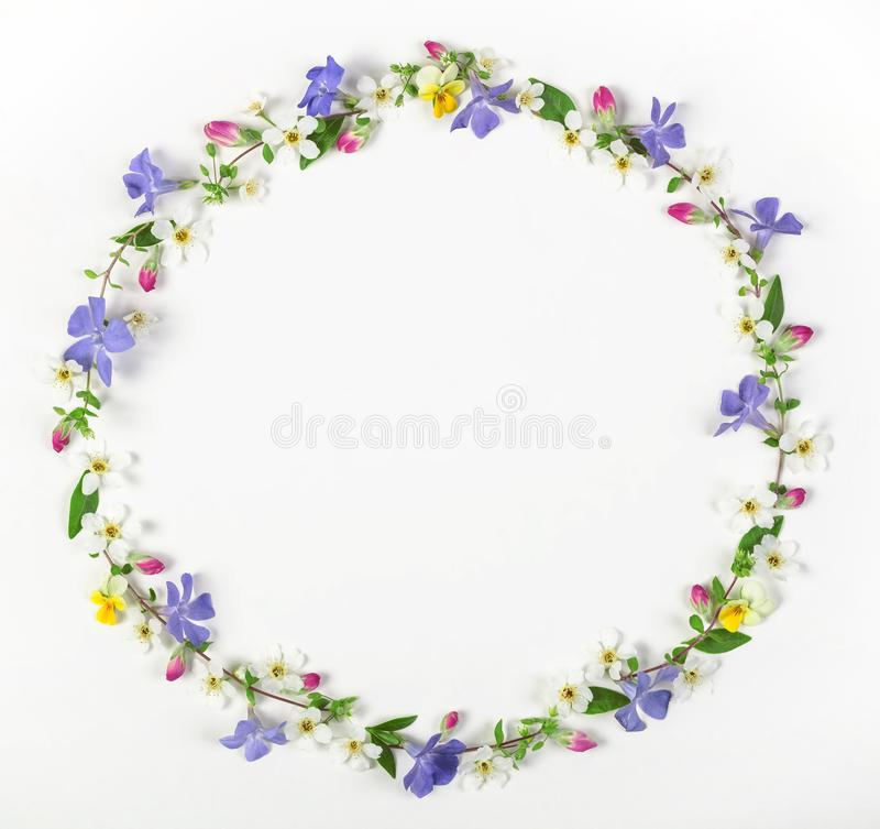 Round frame wreath made of spring wildflowers, lilac flowers, pink buds and leaves isolated on white background. Flat la. Round frame wreath made of spring stock images