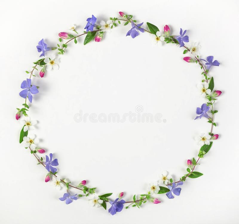 Round frame wreath made of spring wildflowers, lilac flowers, pink buds and leaves isolated on white background. Top view stock photos