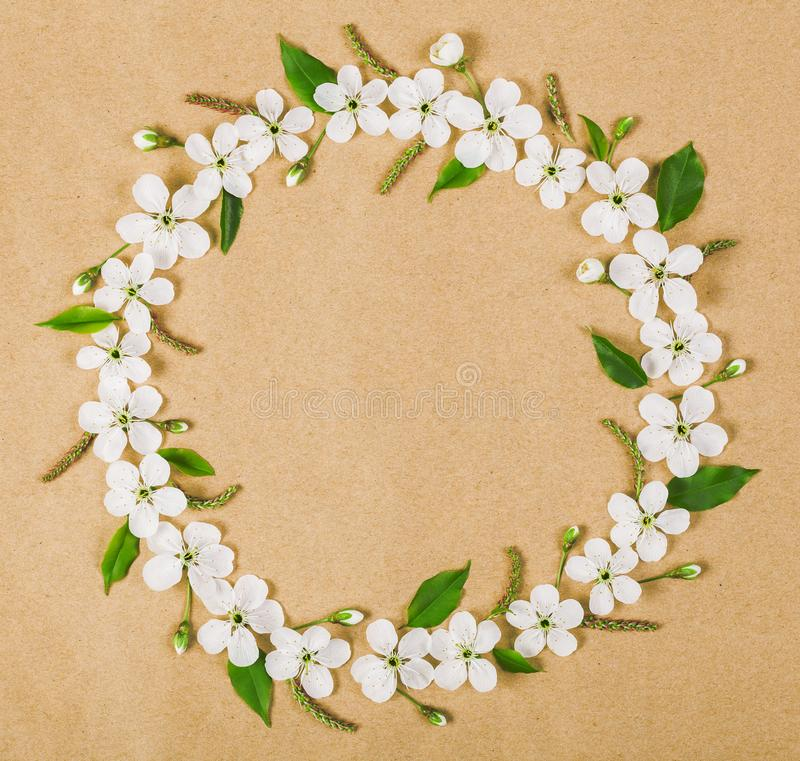 Round frame wreath made of white spring flowers and green leaves on brown paper background. Flat lay. Round frame wreath made of white spring flowers and green stock photography