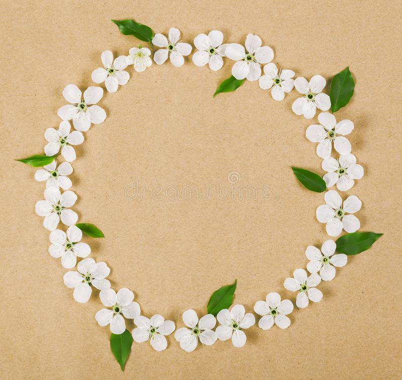 Round frame wreath made of white spring flowers and green leaves on brown paper background. Flat lay royalty free stock images