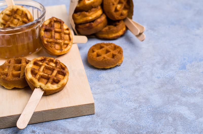 Round fried waffles. On a stick with jam. Selective focus stock photo