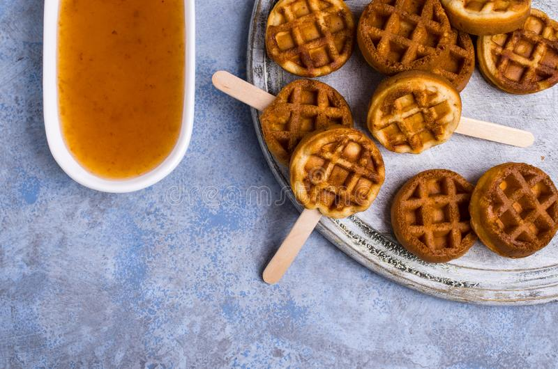 Round fried waffles. On a stick with jam. Selective focus royalty free stock photo