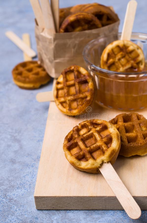 Round fried waffles. On a stick with jam. Selective focus royalty free stock photography