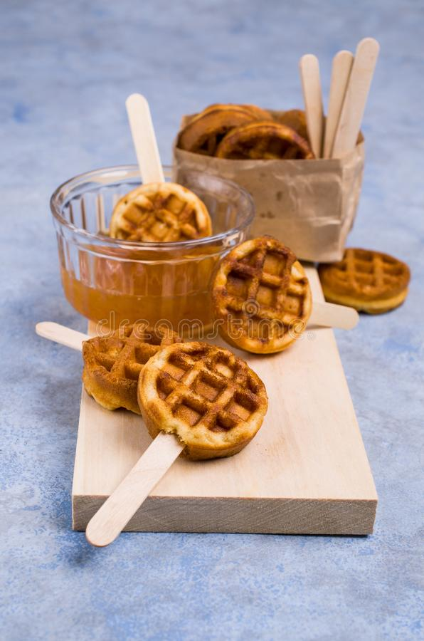 Round fried waffles. On a stick with jam. Selective focus royalty free stock photos