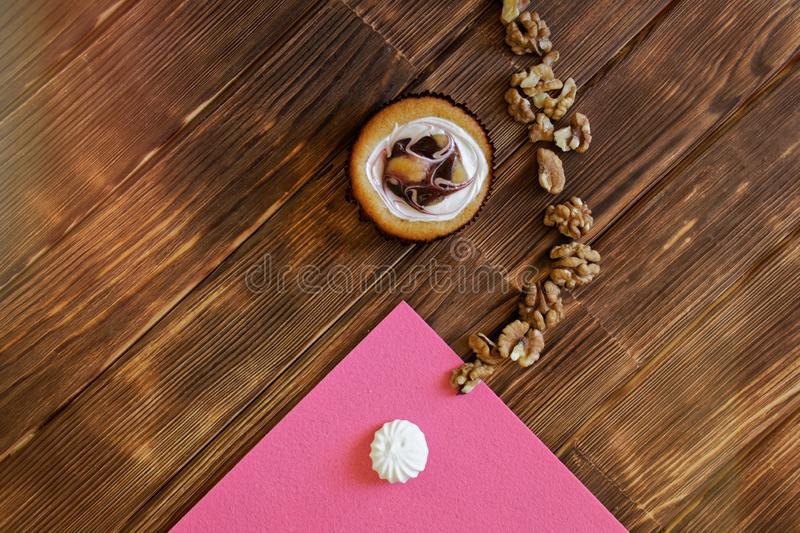 Round fruit cream cake, meringue and peeled walnuts on a pine planks table. Minimalism. Natural brown and pink background. View stock photo