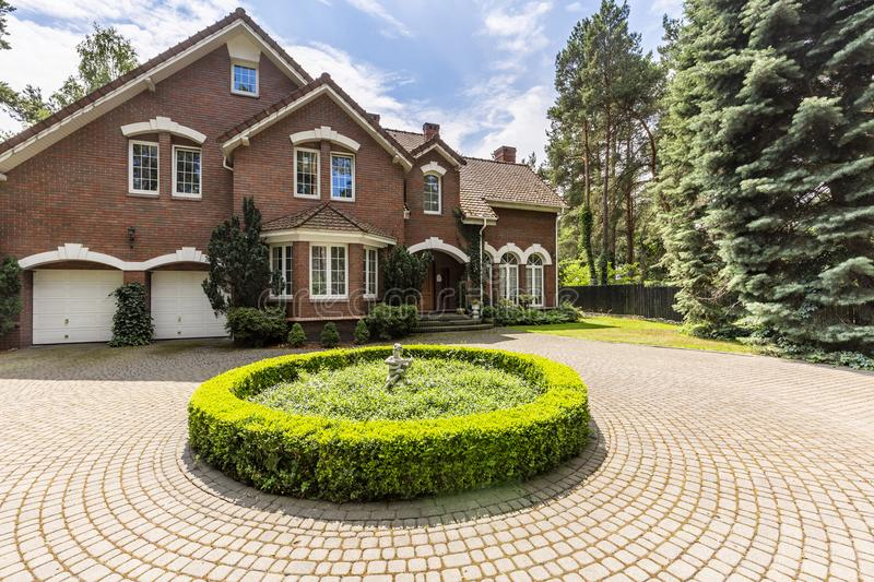 Round garden on driveway of english house in the forest during s. Ummer stock photo