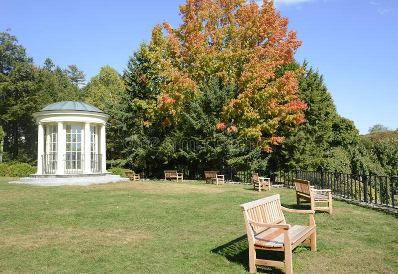 Round gazebo and wood park benches stock images
