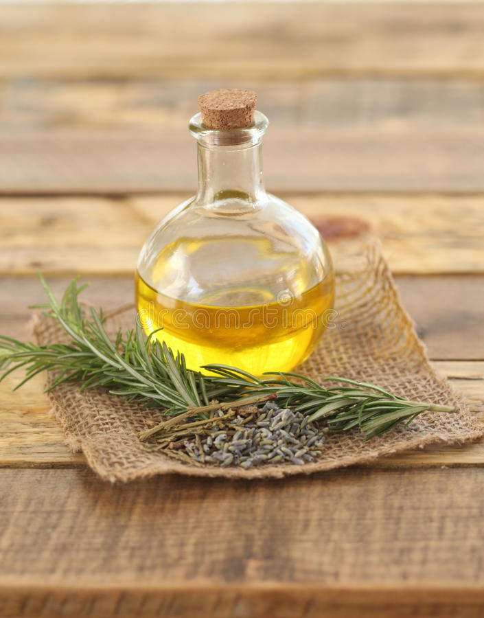 Round Glass Bottle of Oil with Herbs. Round glass bottle filled with herbal olive oil with cork and a rosemary sprig and lavender buds on a rustic wooden surface royalty free stock image