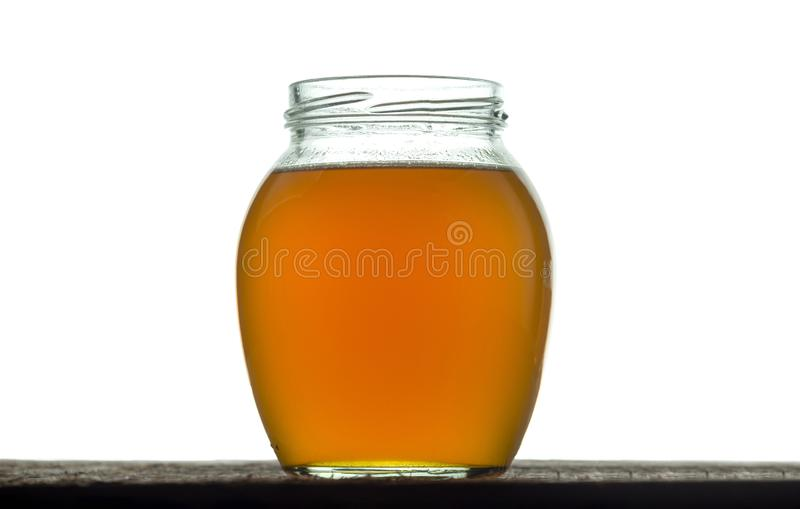 Round glass jar with freshly prepared ghee butter. On a white stock photo