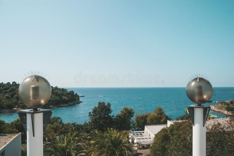 Round glass lanterns on the background of the sea coast. Shoreline lighting with energy-saving lamps royalty free stock photography