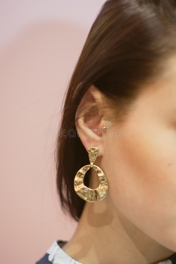 round gold earrings on the ear of a brunette on a pink pastel background royalty free stock image