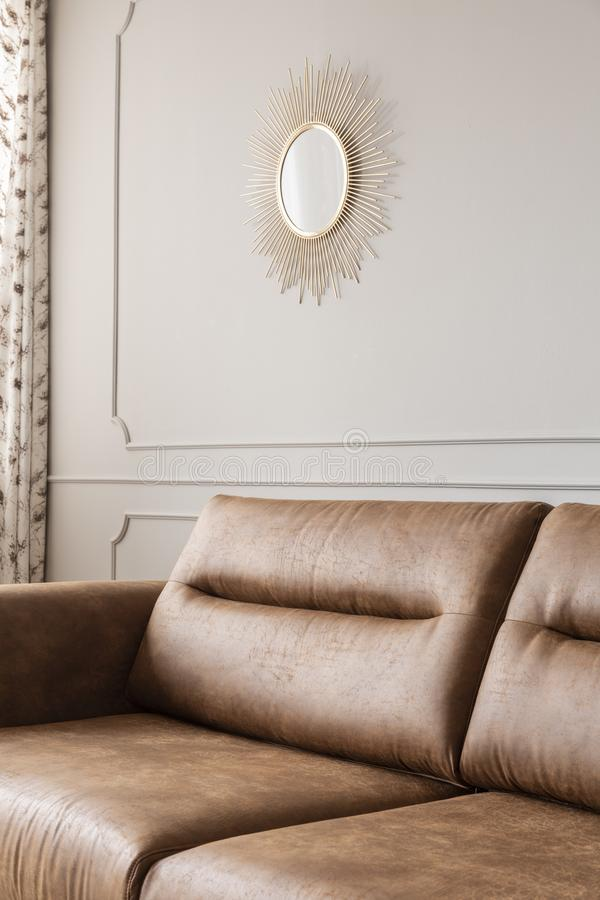 Round gold mirror on the wall with molding in bright sitting room interior with leather brown couch in the real photo stock image