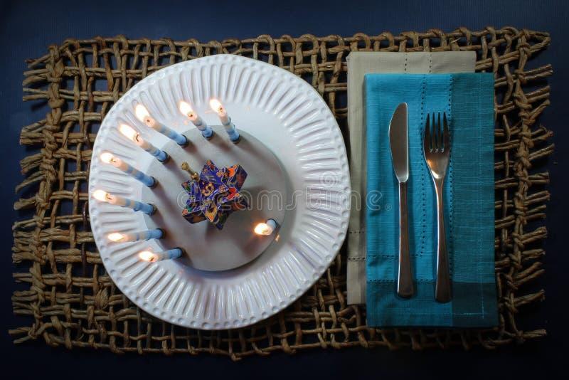 Round Hanukkah menorah on a white handmade plate with Star of David dreidel stock images