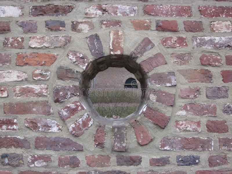 Round hole in a brick wall with a view on wall and garden with l stock photos