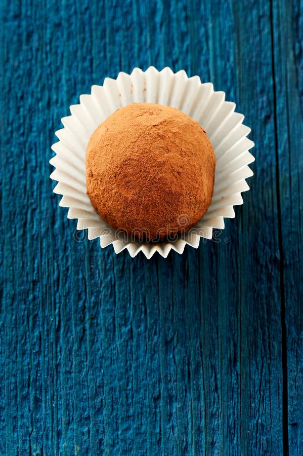 Round homemade vegan cocoa truffle in paper plate on deep blue b stock images