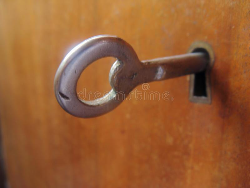 The round key sticks out of the keyhole and is ready to open the door stock photography